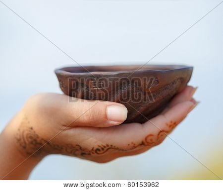 Female hand with traditional Indian wedding henna mehendi pattern holding a clay cup with widespread ethnic symbols.