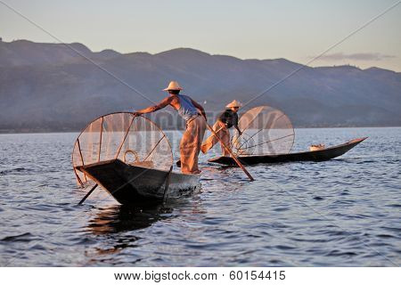 INLE LAKE, MYANMAR - DECEMBER 12, 2013: Fishermen at Inle Lake, Shan State, Myanmar  Intha people possess the leg-rowing style and the unique coop-like fishing equipment