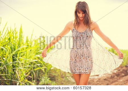 Gorgeous Romantic Girl Outdoors. Beautiful  Model in Short Dress in Field. Long Hair Blowing in the Wind. Backlit, Warm Color Tones