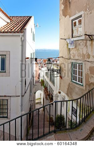 One of the narrow streets of Alfama with the typical cobblestone staircases (Beco da Corvinha). Alfama, Lisbon, Portugal