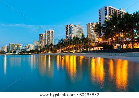 Beach At Waikiki With Buildings And Reflections