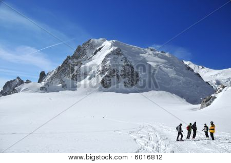 A Group Of Skiers, A High Mountain And A Large Glacier