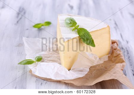 Tasty Camembert cheese with basil, on wooden table