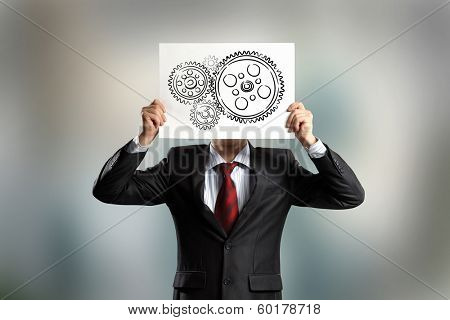 Businessman hiding his face behind paper with drawing