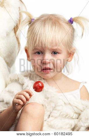 Little crying girl with a candy over white