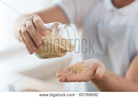 cooking and home concept - close up of male emptying jar with quinoa