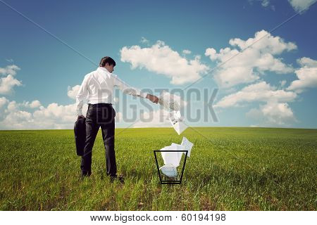 Businessman In A Green Field Throws Papers In The Trash