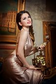 stock photo of manor  - Young beautiful luxurious woman in elegant dress smiling holding a vintage telephone - JPG