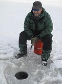 stock photo of fishing bobber  - Happy Man sitting on an orange five gallon bucket Ice Fishing with pole in hand over bobber in hole in ice - JPG