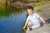 Little beautiful boy sitting near the water