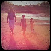 mother and children walking on beach in sunset with view finder effect