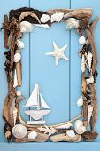 Sea shell and driftwood with small decorative boat forming an abstract border over wooden blue backg