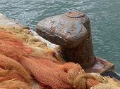 stock photo of bollard  - bollard with fishing net in a harbour - JPG