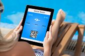 Girl Lying On A Deck Chair By The Pool And Holding A Tablet With Mobile Wallet And Plane Ticket On A