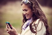 stock photo of coat  - smiling young woman reading message on her smartphone outdoor shot - JPG