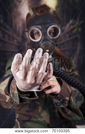 Young girl wearing military uniform and gas mask over dark background