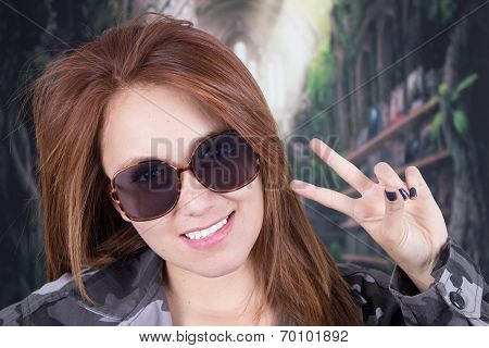 Young smiling girl wearing military uniform and sunglasses