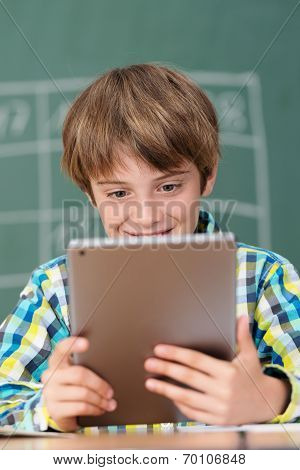 Smiling Little Boy Using A Tablet In Class