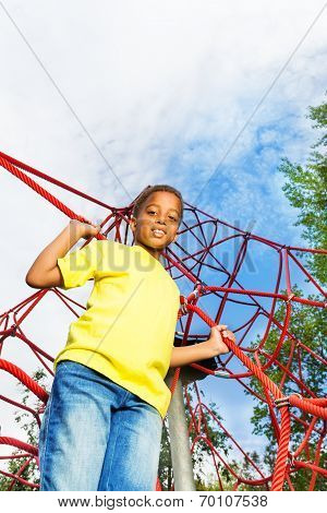 African boy holds and stands on red ropes