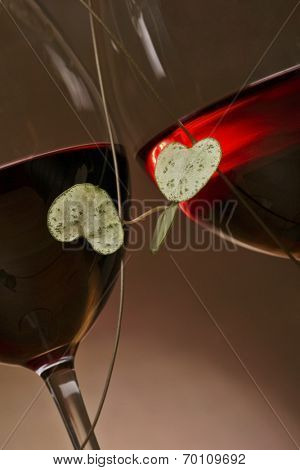 loveheart vine encircling two glasses of red wine, suggestion of romance.