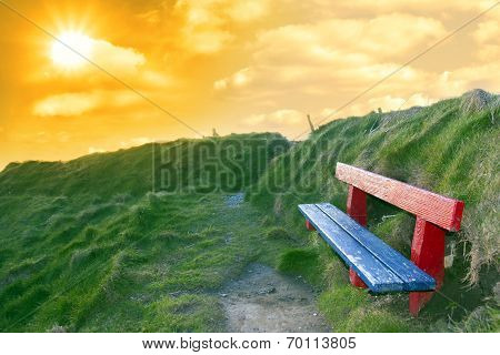 Bench On A Cliff Edge At Sunset