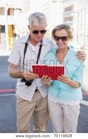 Happy tourist couple using tour guide book in the city on a sunny day