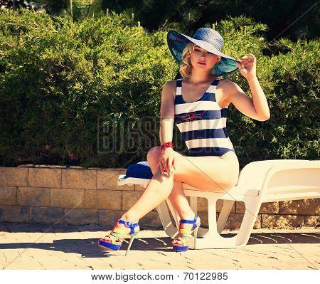 Woman Sunbathing On A Chaise Lounge