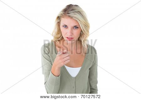 Pretty young blonde pointing at camera on white background