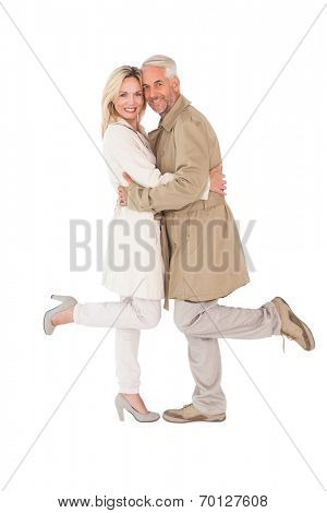 Happy couple posing in trench coats on white background