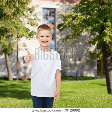 advertising, summer, gesture, people and childhood concept - smiling little boy in white blank t-shirt over campus background