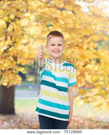 happiness, childhood, seasons and people concept - smiling little boy in casual clothes showing thumbs up over autumn park background