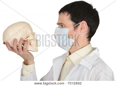 Student Medical School In Mask Looks At Skull