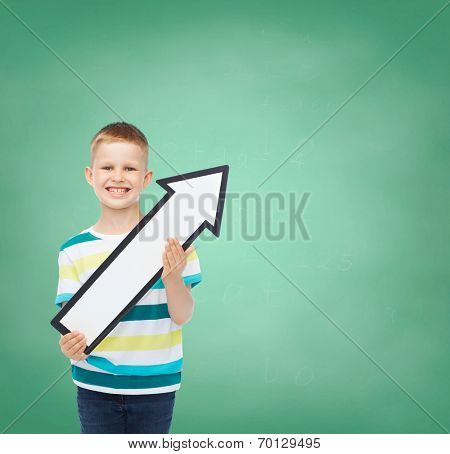advertising, direction, education and childhood concept - smiling little boy with white blank arrow pointing up over green board background