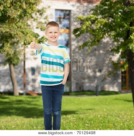 happiness, childhood, gesture, leisure and people concept - smiling little boy in casual clothes showing thumbs up over campus background