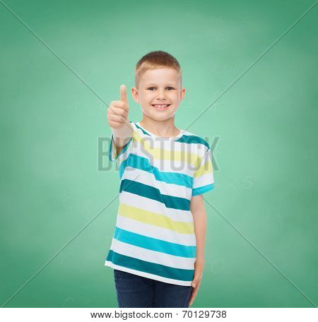 happiness, childhood, school, education and people concept - smiling little boy showing thumbs up over green board background