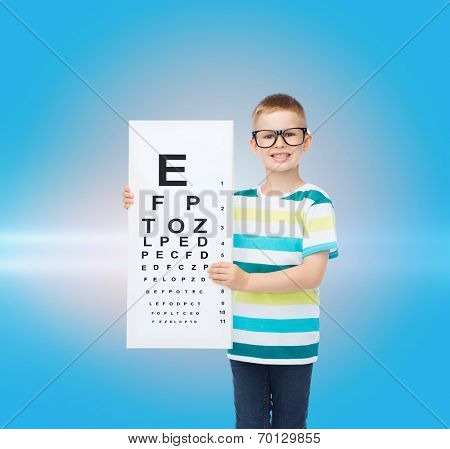 vision, health, childhood, ophthalmology and people concept - smiling little boy in eyeglasses with with eye chart over blue background with laser light