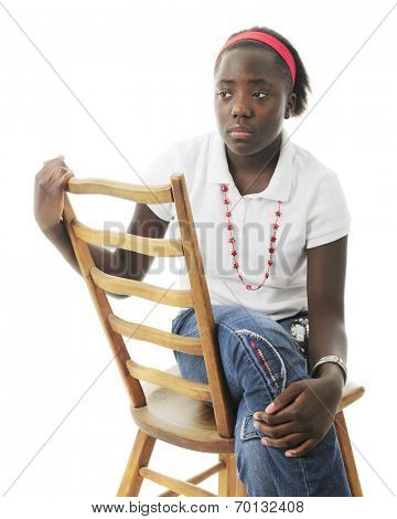 A sad tween girl sitting sideways on a ladder-back chair.  On a white background.