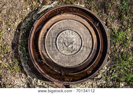 Manhole With Rusty Metal Cover And Water In Its Grooves