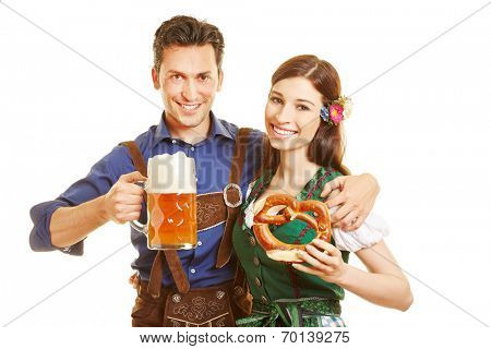 Happy couple with beer and pretzel at Oktoberfest in Bavaria
