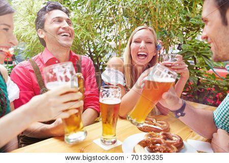 Happy friends laughing in beer garden in summer in Bavaria