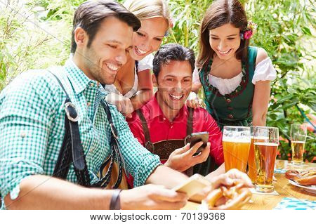 Happy friends in beer garden looking together at smartphones