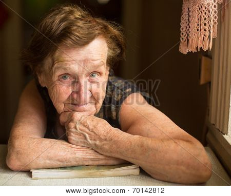 Portrait of an elderly woman with a book or directory in home.
