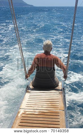 A lady sitting on the back of a motorboat