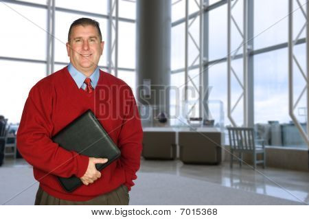 Businessman With Leather Folder In Lobby