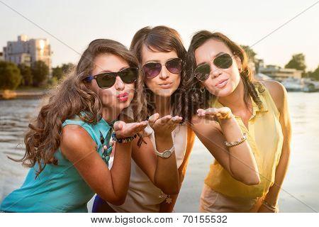 Three stylish girlfriends in sun glasses send air kiss to camera