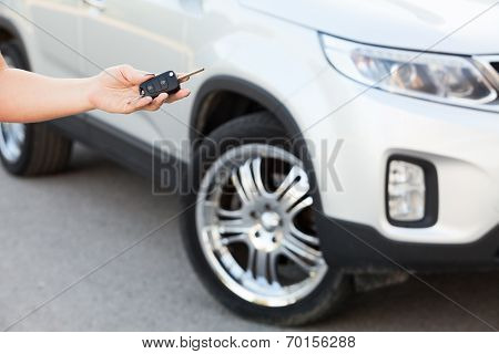 Female Hand Holding Car Key With Suv On Background