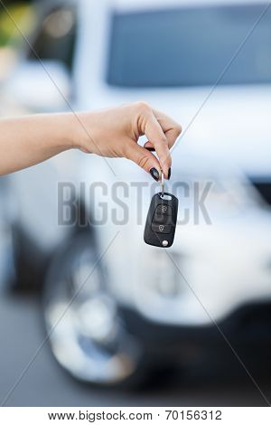 Ignition Key Hanging In Female Hand With Defocused Car