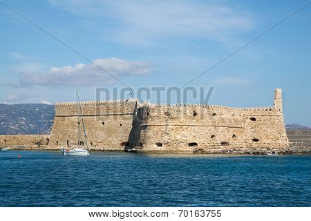 Greek Island Crete In The Cyclades: Sightseeing On The Old Port With Fort And Boats.