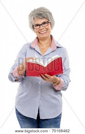 Happy elderly woman holding and reading a book
