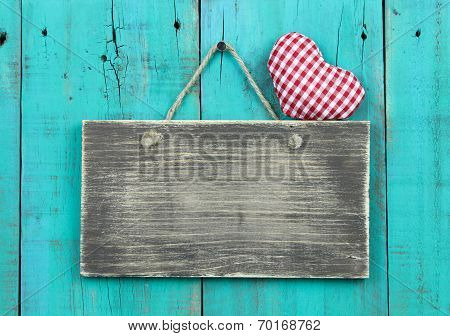 Blank distressed sign with red checkered heart hanging on rustic antique blue background